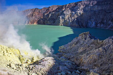 Smoke Of Sulfur Toxic Gas In The Acidic Crater Lake Of Kawah Ijen Volcano, Banyuwangi, East Java, Indonesia. Mount Ijen Is The Famous Tourist Attraction, Where Sulfur Is Mined.