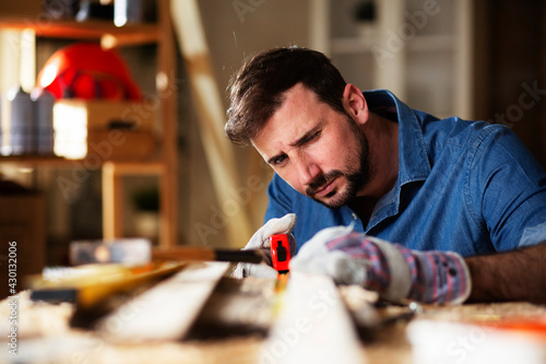 Young male carpenter working in workshop Fototapete