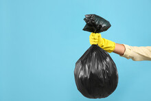 Woman Holding Full Garbage Bag On Light Blue Background, Closeup. Space For Text