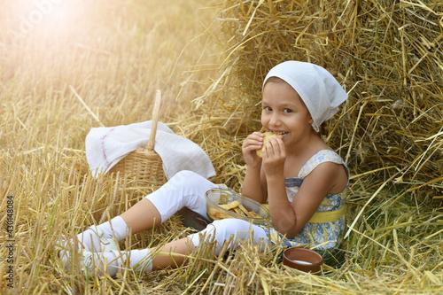 Obraz na plátne little girl eating on a haystack