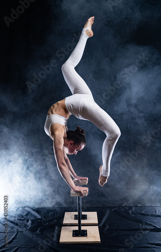 Flexible circus artist - female acrobat doing handstand on the back and smoker background Fototapet
