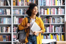 Portrait Of Joyful Pretty African American Female Student Standing Against Background Of Bookshelves In University Library Holding Laptop And Backpack Looking To The Side, Smiling Pleasant