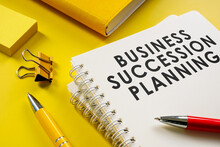Business Succession Planning Documents On The Yellow Surface.
