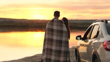 Happy Enamored Travelers Man And Woman Cover Themselves With A Blanket Next To Car And Admire Beautiful Sunset On Beach. Tourists Hug Next To Car, Admire Sunrise Of River. Free Travelers By Car.