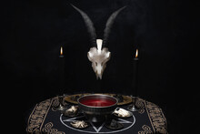 Pentagram And Devil Symbols With Black Burning Candles On Witch Wooden Table In The Dark. Esoteric, Gothic And Occult Background, Halloween Mystic Concept.