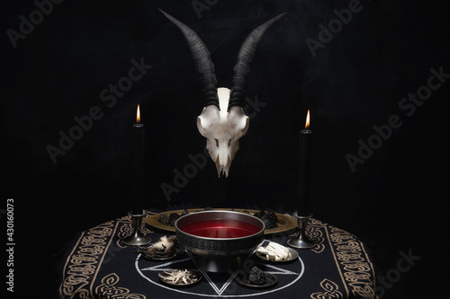 Fototapeta Pentagram and devil symbols with black burning candles on witch wooden table in the dark