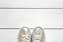 Child Metallic Silver Sneakers On White Wood Board Background Texture With Copy Space. White Sneakers For Girls. Top View