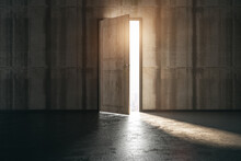 Business Ventures And Initiatives Concept With Bright Sunlight Falling On Concrete Floor From Opened Door In Wooden Wall