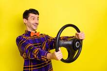 Profile Side Photo Of Young Man Happy Smile Hold Steering-wheel Drive Auto Look Empty Space Isolated Over Yellow Color Background