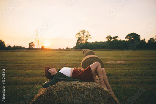 Fotografia, Obraz Carefree woman in hat lying on haystack in sunset light enjoying evening in summer field