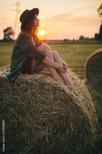 Obraz na plátne Beautiful woman relaxing on haystack in sunset light in evening summer field