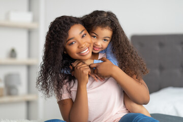 Love between parent and child. Positive little black girl hugging her mom on bed at home