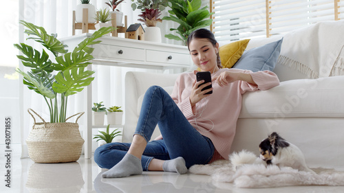 Obraz Young attractive beautiful asian lady wear earphone happy listen digital podcast online channel for reskill upskill mindfulness break at home in quarantine social distance self isolate on sofa couch. - fototapety do salonu