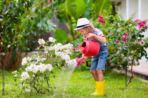 Obraz na plátně Child gardening. Boy with watering can in garden.