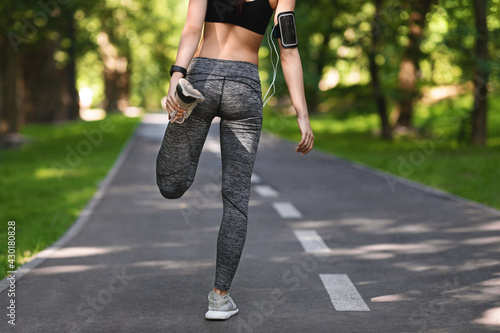 Fotomural Unrecognizable female jogger preparing for run in city park, stretching leg musc