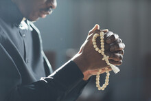 Close-up Of African Man Holding Beads In His Hands And Praying In The Church