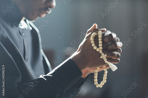 Foto Close-up of African man holding beads in his hands and praying in the church
