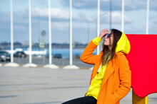 Millennial Hipster Girl In Lilac Sunglasses, Orange Coat, Yellow Hoodie Posing At Urban Background. Trendy Colorful Casual Outfit. Street Style. Fashion Lookbook Concept