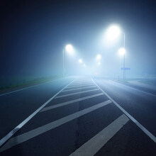 Panoramic View Of The Illuminated New Highway In A Fog At Night, Street Lights Close-up. Moonlight. Dark Urban Scene. Europe. Transportation, Logistics, Travel, Tourism, Road Trip, Freedom, Driving
