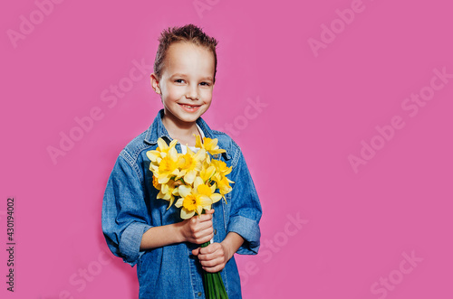A cute smiling boy looks at the camera and holds a bouquet of yellow narcisses in his hands Wallpaper Mural