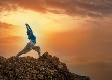 Young Woman In Warrior Yoga Pose Practice On Mountain Rock At Sunrise