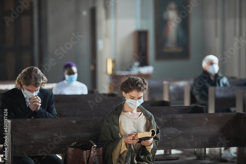 Fotografia Young woman in protective mask sitting on bench and reading the Bible in the chu