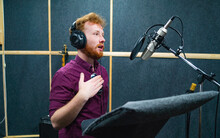 Expressive Face Of Bearded Man With Red Curly Hair Wear Headphones Near Microphone Who Makes Professional Dubbing On A Voice Recording Studio