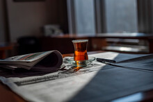 A Glass Of Turkish Tea And With Pen On The Newspaper