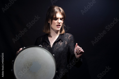 portrait of a smiling young beautiful drummer girl, in black, holding a snare drum, posing Fototapeta