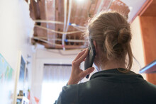 Woman Talking To Homeowner's Insurer While Inspecting Kitchen Ceiling