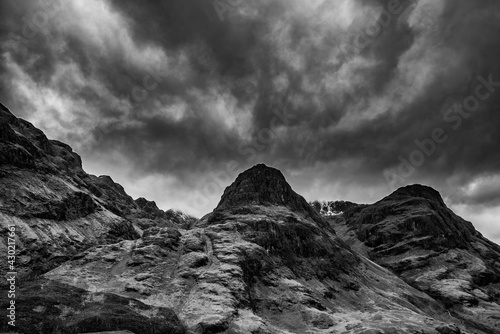 Majestic moody  black and white landscape image of Three Sisters in Glencoe in Scottish Highlands on a wet Winter day wit high water running down mountains - fototapety na wymiar