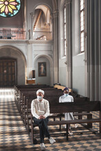 People In Masks Sitting On The Bench In Old Beautiful Church And Praying