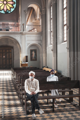 Fototapeta People in masks sitting on the bench in old beautiful church and praying obraz