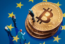 Business Meeting About The Investment Decision For Bitcoin Concept: Miniature Businessman Figurines Standing Near The Pile Of Shiny Golden Bitcoin On European Union Flag.