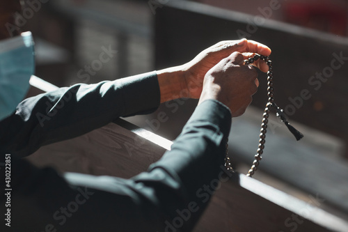 Canvas Print Close-up of priest in mask holding rosary beads while sitting in front of the al