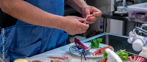 Fotografija レストランのキッチンで料理を盛り付けるシェフの手元