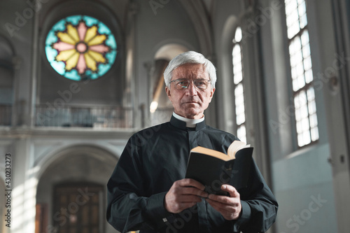 Obraz na plátně Portrait of senior priest holding the Bible and looking at camera while standing