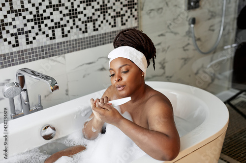 Foto Portrait of nice good-looking african lady sawing nails while taking bath