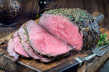 Traditional Barbecue Dry Aged Angus Roast Beef Steak With Yorkshire Pudding And Herbs Served As Close-up On A Rustic Wooden Board
