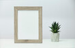 White marble desk with vertical photo frame and a little cactus in concrete flower pot near a gray wall.