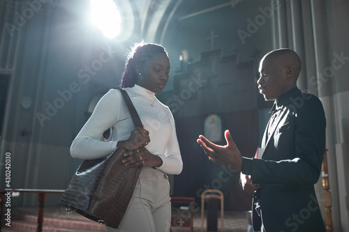 Fotografia African woman talking to priest after ceremony in the church