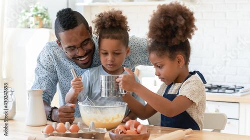 Photo Happy dad teaching two cute preschooler kids to bake