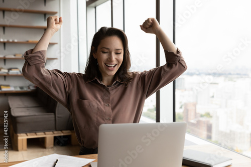 Fotografia Overjoyed young Caucasian female employee look at laptop screen triumph reading good news online
