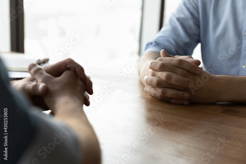 Stampa su Tela Crop close up of male business partners sit at desk with hands clasped talk at meeting in office