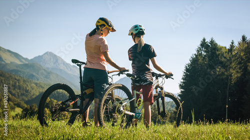 Two females on mountain bikes talking and looking at beautiful green nature.