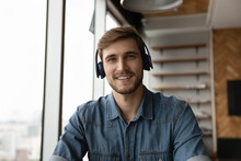 Headshot Portrait Of Smiling Young Caucasian Man In Earphones Talk Speak On Video Call Online With Client. Screen View Of Happy Male In Headphones Have Webcam Zoom Conference. Virtual Event Concept.