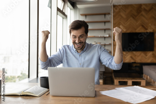 Photographie Excited young Caucasian businessman look at laptop screen triumph reading good email or news online
