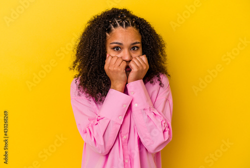 Slika na platnu Young african american woman isolated on yellow background biting fingernails, nervous and very anxious