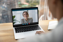 Rear Over Shoulder View Of Man Talk Speak With Smiling Female Colleagues On Video Online Call On Laptop. Diverse Businesspeople Have Webcam Digital Virtual Zoom Meeting. Communication Concept.