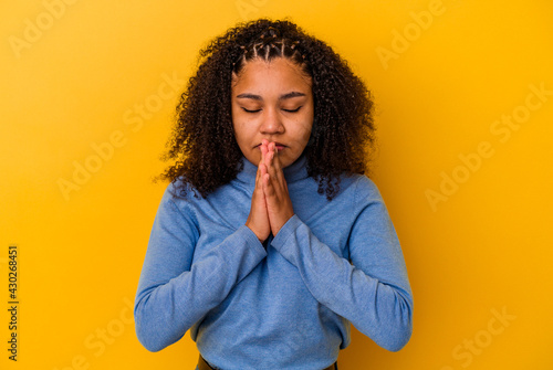 Fototapeta Young african american woman isolated on yellow background praying, showing devotion, religious person looking for divine inspiration